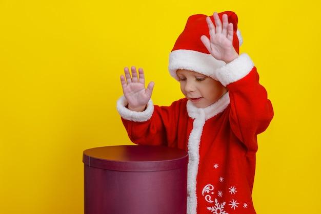 Un enfant déguisé en père noël est heureux de jouer sur un coffret cadeau comme un tambour.