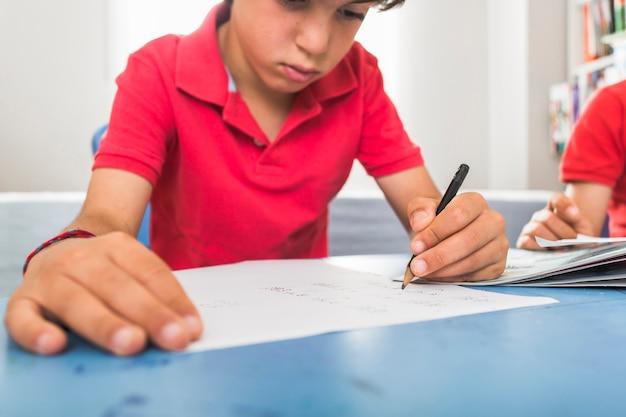 Enfant dessin avec un stylo à table