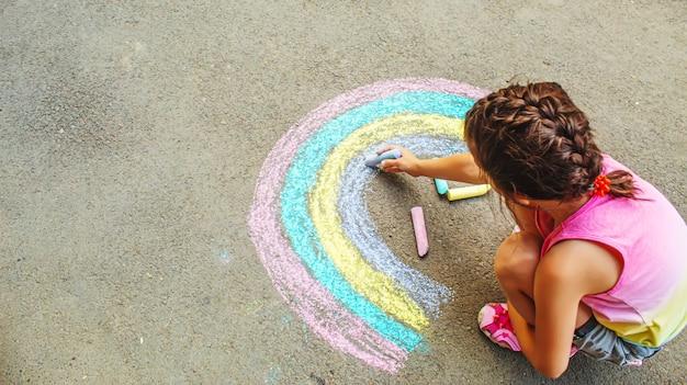 Un enfant dessine un arc-en-ciel sur l'asphalte. mise au point sélective. enfant.