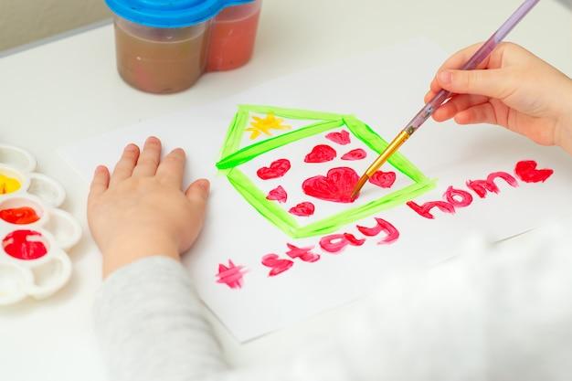 L'enfant dessine le cœur à l'intérieur de la maison