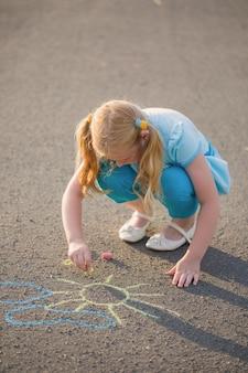 L'enfant dessine une craie sur l'asphalte