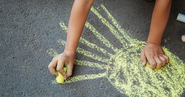 L'enfant dessine à la craie sur le trottoir. mise au point sélective.arts
