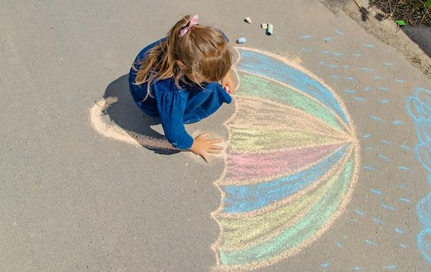 Enfant dessine à la craie sur le trottoir