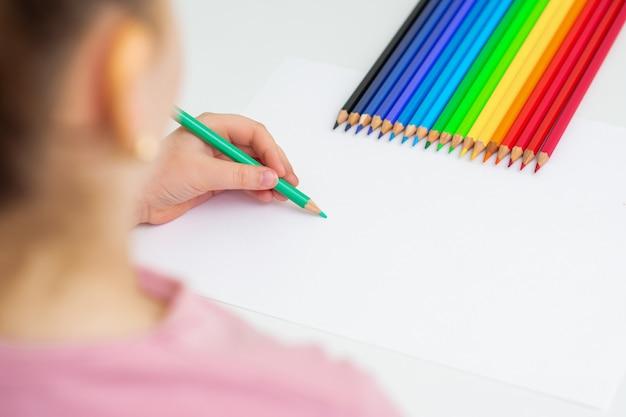 L'enfant dessine avec des crayons de couleur.