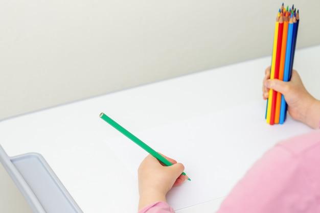 L'enfant dessine avec des crayons de couleur