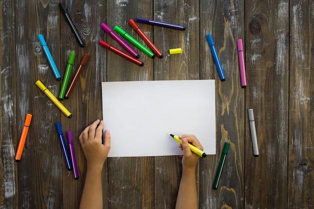 Enfant dessine dans un cahier