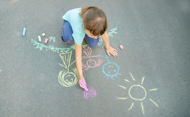 Enfant dessine une famille sur le trottoir avec de la craie. mise au point sélective.
