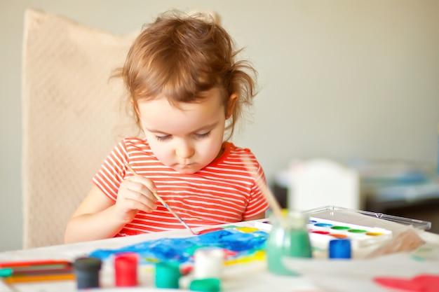 Un enfant dessine une fleur avec des peintures colorées sur le papier.