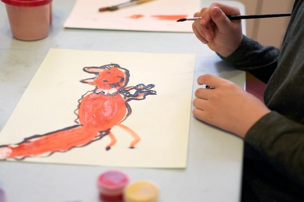 L'enfant dessine une image pendant le cours d'art en ligne sur téléphone portable, quarantaine covid-19, auto-isolement, concept d'éducation en ligne, enseignement à domicile. enfants à la maison, jardin d'enfants fermé, homelerning. garçon de 6 ans.