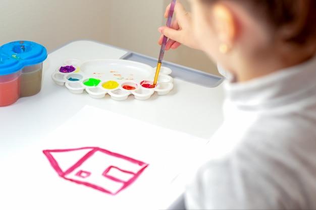 Enfant dessine la maison avec des aquarelles