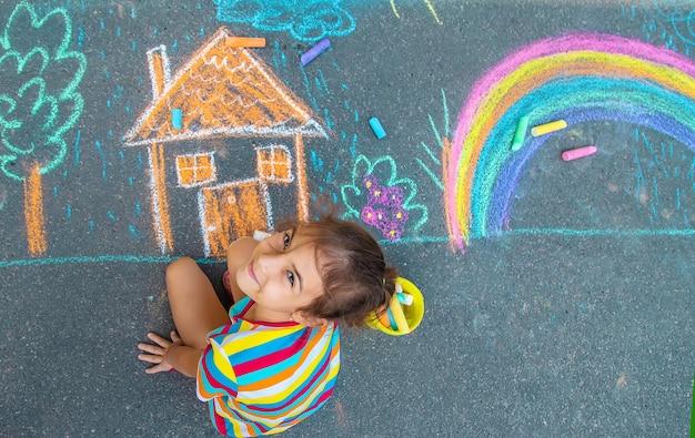 L'enfant dessine une maison et un arc-en-ciel sur l'asphalte avec de la craie