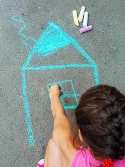 L'enfant dessine la maison à la craie sur l'asphalte. mise au point sélective. dessiner.