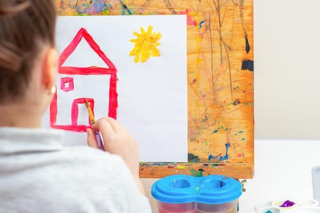L'enfant dessine une maison.