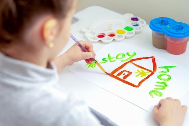 L'enfant dessine la maison.