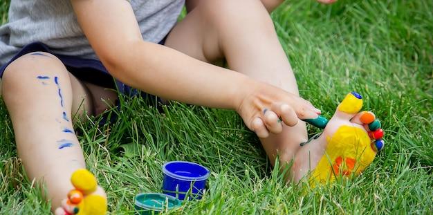 L'enfant dessine un motif sur la jambe. un dessin amusant avec des couleurs vives sur le corps. mise au point sélective