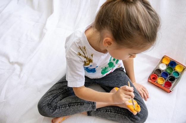 L'enfant dessine un motif sur son pied avec un pinceau