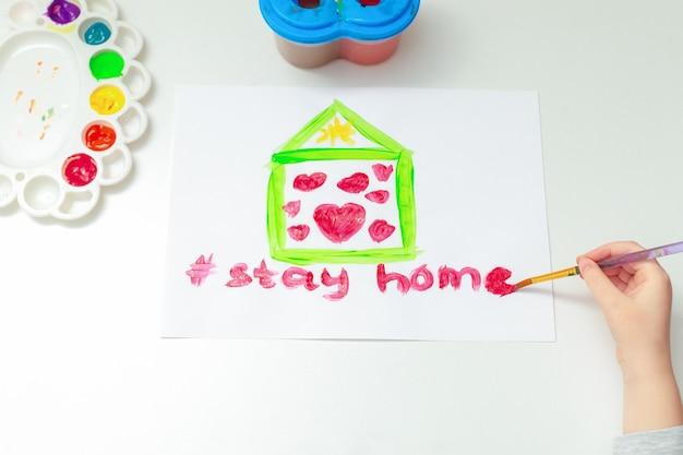 L'enfant dessine des mots restez à la maison sous une maison peinte avec des coeurs rouges à l'aquarelle sur une feuille blanche