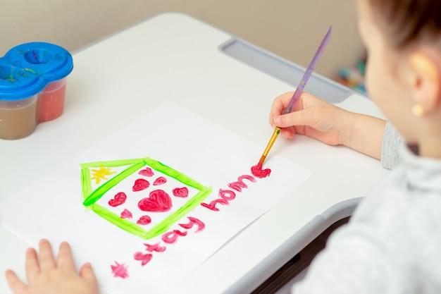 L'enfant dessine des mots restez à la maison