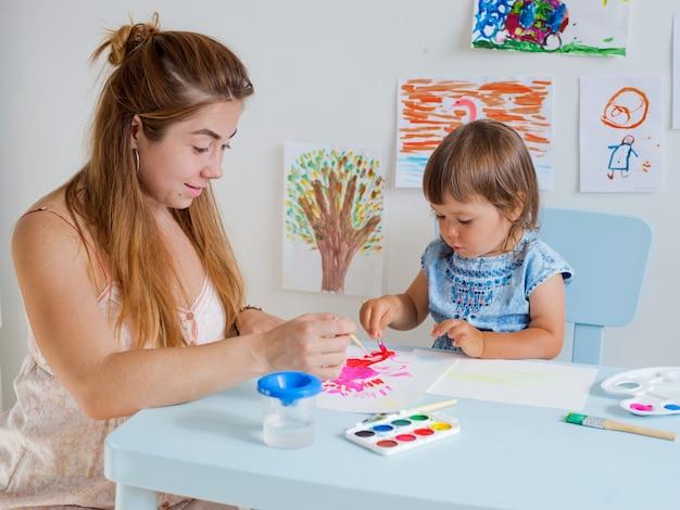 Enfant dessine avec le professeur