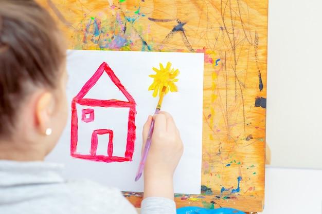 L'enfant dessine un soleil jaune avec une maison rouge.