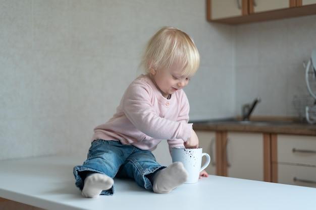 Enfant de deux ans dans la cuisine avec une tasse dans ses mains. portrait d'enfant blond dans la cuisine.