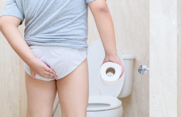 L'enfant a la diarrhée en tenant son cul dans les toilettes,