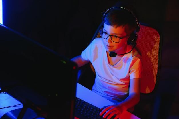 Un enfant diffuse un jeu informatique en ligne, un garçon diffuse dans des écouteurs sur fond d'éclairage rvb