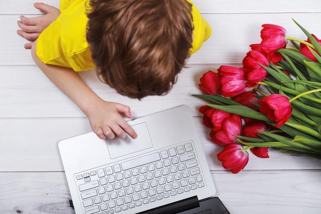 Enfant discutant sur un carnet avec des tulipes à bouquet pour sa mère.