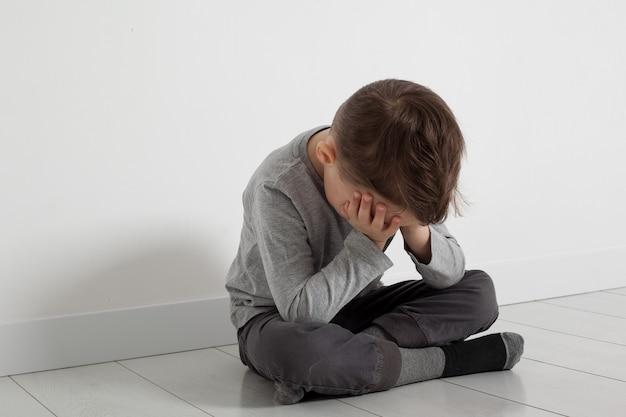 Un enfant dont la dépression est assis par terre