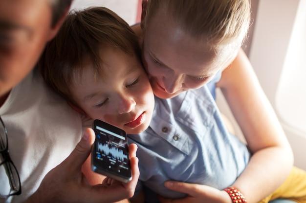 Enfant dormant avec de la musique sur un téléphone portable en avion