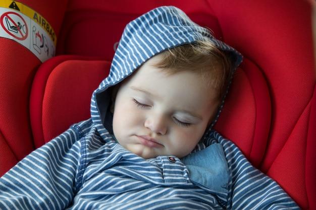L'enfant dort dans le siège d'auto