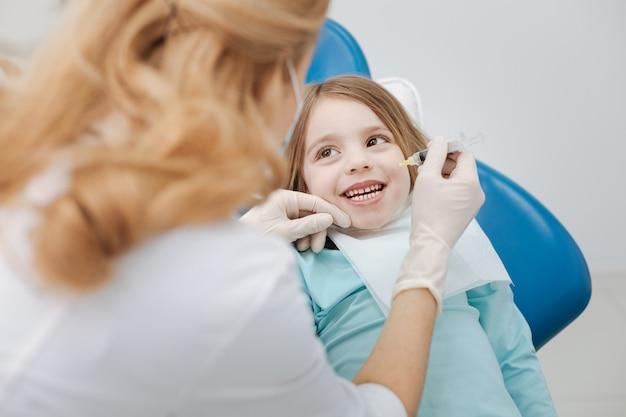 Enfant doux brillant émotionnel se comportant bien et montrant ses dents pendant que le médecin exécute une procédure nécessaire