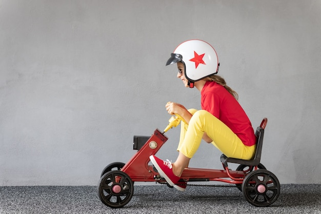 Enfant drôle conduisant une voiture de course. concept de succès et de victoire