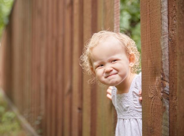 L'enfant drôle dans des vêtements légers regarde hors d'un trou dans la journée ensoleillée d'été de barrière