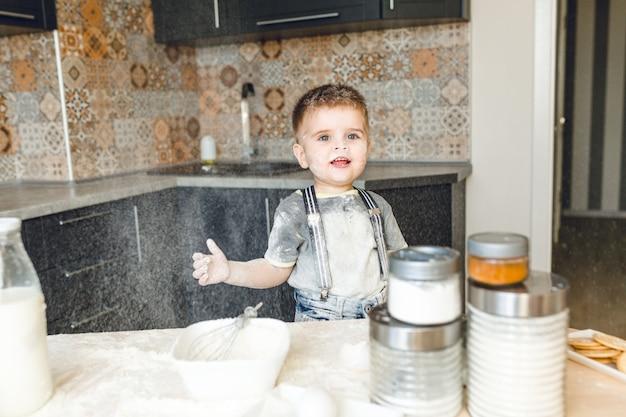Enfant drôle debout dans une cuisine roustique jouant avec de la farine et le jetant en l'air.