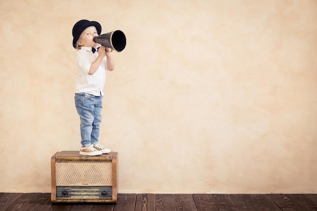 Enfant drôle jouant à la maison. kid criant à travers un mégaphone vintage. communication et concept de cinéma rétro