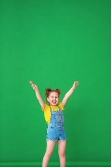 Enfant drôle avec les mains levées en l'air. fille avec une sucette est drôle