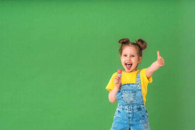 Un enfant drôle montre un geste d'approbation, avec une sucette sur un bâton sur sa langue.