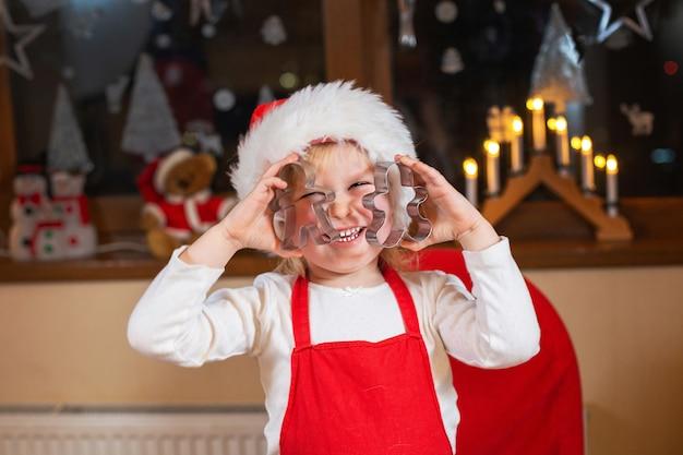 L'enfant drôle prépare les biscuits de cuisson de pâte dans la cuisine