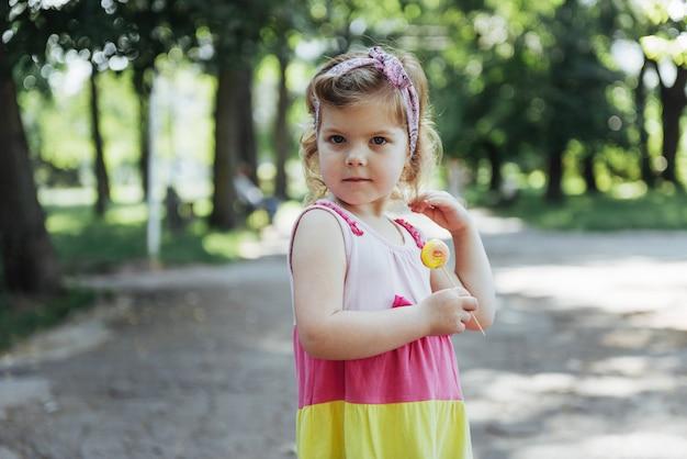 Enfant drôle avec sucette de bonbons, heureuse petite fille