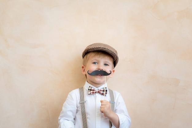Enfant drôle tenant une fausse moustache. heureux enfant jouant à la maison