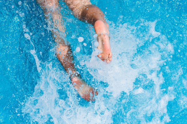 Enfant éclaboussant dans l'eau fraîche d'une piscine en été