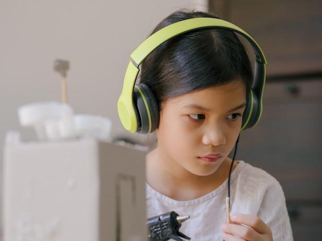 Enfant de l'école avec de l'artisanat recyclé et recyclé. le recyclage aide à sauver la planète, apprend aux enfants à générer moins de déchets. activités créatives pour enfants.