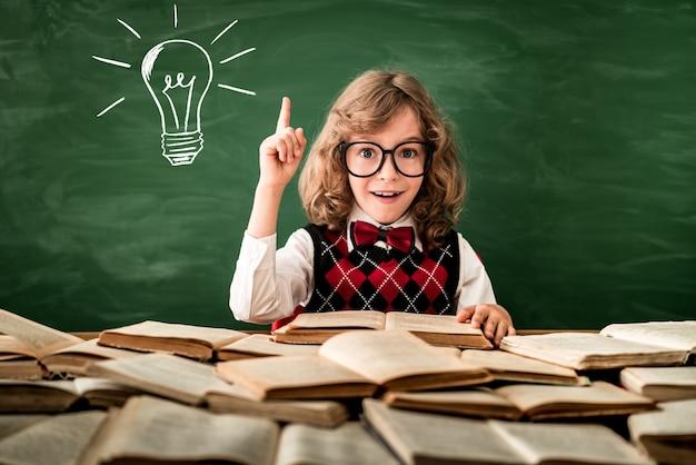 Enfant de l'école en classe happy kid contre le concept de l'éducation tableau noir vert