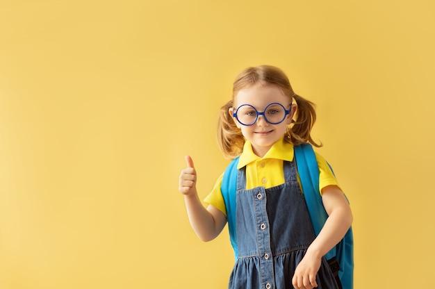 Enfant de l'école dans des verres avec sac à dos isolé sur fond jaune montrant le pouce vers le haut 1 septembre