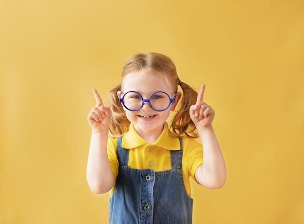 Enfant de l'école drôle dans des verres isolé fond jaune doigts pointant vers l'espace de copie