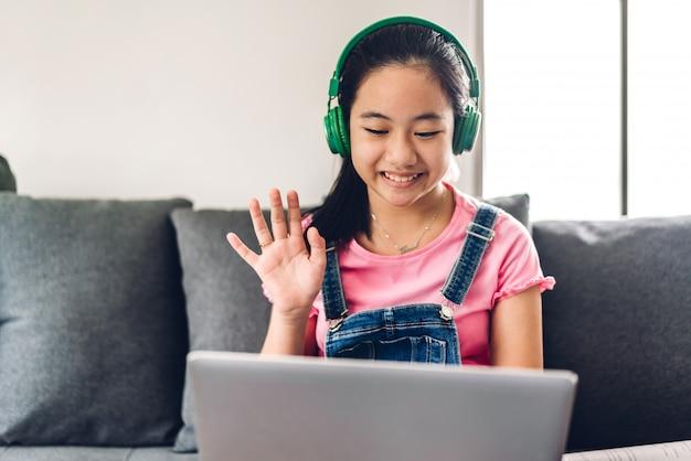 Enfant de l'école petite fille apprenant et regardant un ordinateur portable à faire ses devoirs étudier les connaissances avec l'éducation en ligne e-learning system. conférence vidéo pour enfants avec le professeur tuteur à la maison