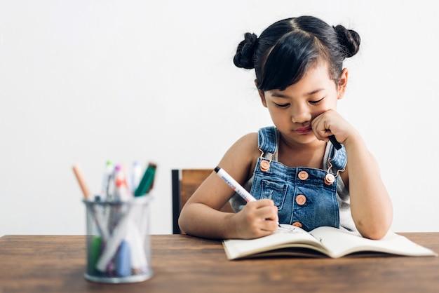 Enfant de l'école petite fille d'apprentissage et d'écriture dans un cahier avec un crayon à faire leurs devoirs à la maison.