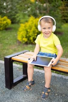 Un enfant avec des écouteurs et une tablette apprend à distance