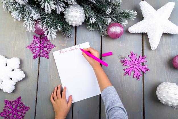 Enfant écrit la lettre aux mains du père noël kid